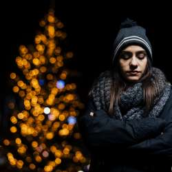Woman in front of lit up tree, looks sad and lonely